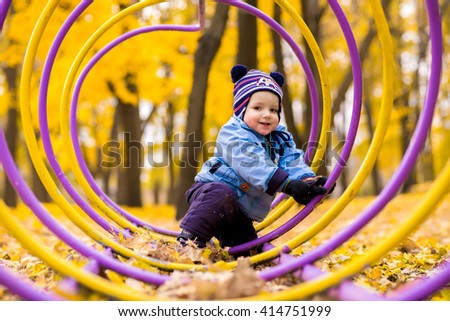 Little baby boy in the autumn park sitting in leaves - stock photo