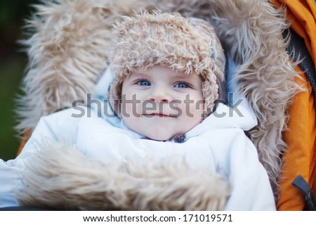 Little baby boy in warm winter clothes and orange pram outdoor