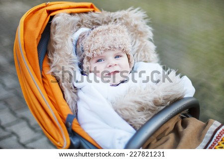 Little baby boy in warm winter clothes and orange pram outdoor - stock photo