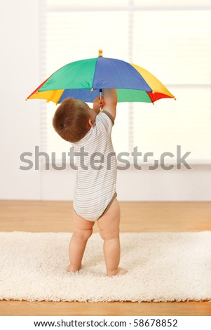 Little baby boy opening a colorful umbrella - stock photo
