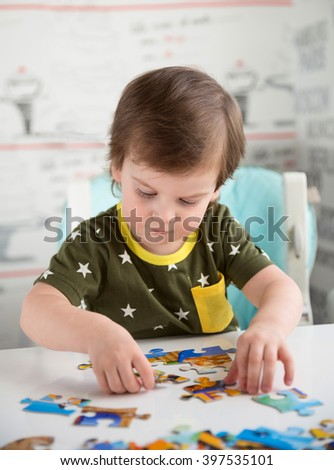Little baby boy or toddler playing with a puzzle, child development concept