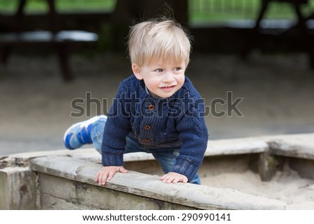 Little baby boy outdoors playing in sandbox. - stock photo
