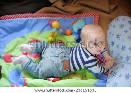 Little baby boy playing on bright carpet at home - stock photo