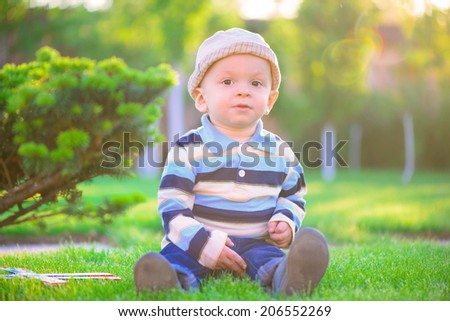 Little baby boy playing on green grass - stock photo