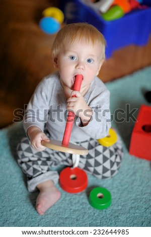 Little baby boy playing with bright toy - stock photo