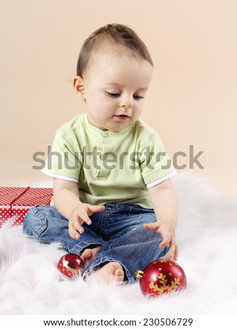Little baby boy playing with christmas balls - stock photo