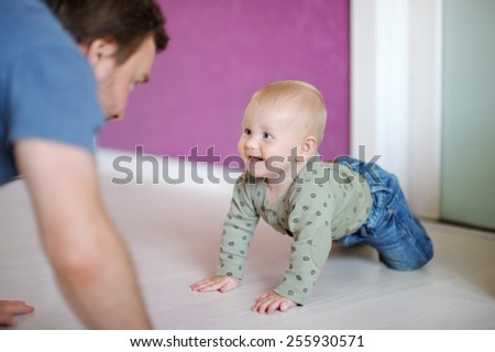 Little baby boy playing with his father at home - stock photo