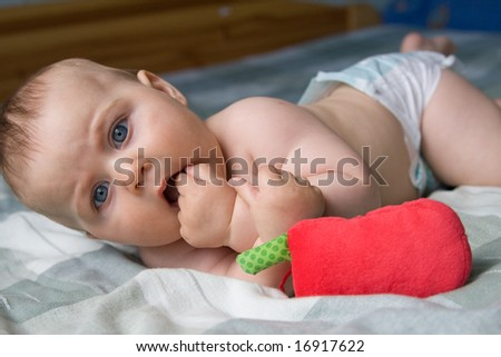 little baby boy playing with toy and sucking his fist