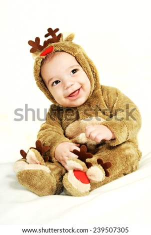 little baby boy portrait wearing a fur Christmas deer costume and smiling at the camera isolated on White background - stock photo