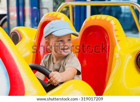 Little baby boy riding car in amusement park - stock photo