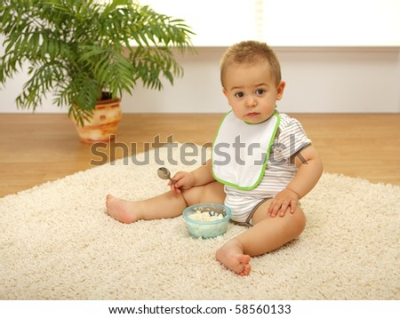 Little baby boy sitting alone on white carpet and eating