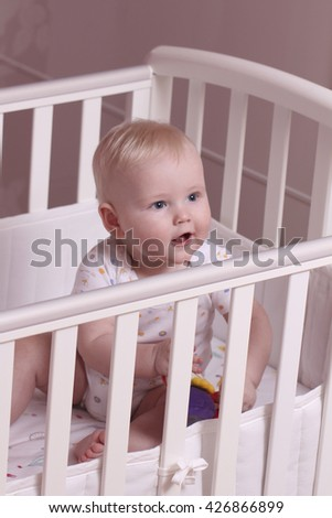 Little baby boy sitting in a crib