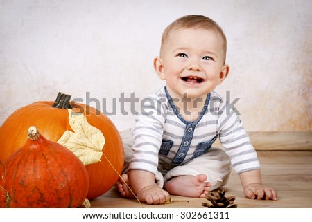 Little baby boy sitting on the floor with pumpkins - stock photo