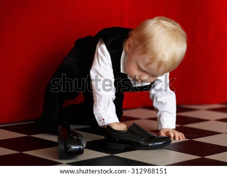 Little baby boy trying to wear patent leather shoes - stock photo
