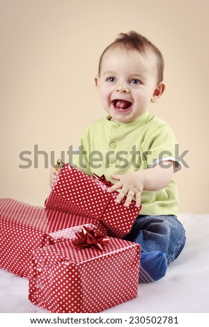 Little baby boy unwrapping christmas presents - stock photo
