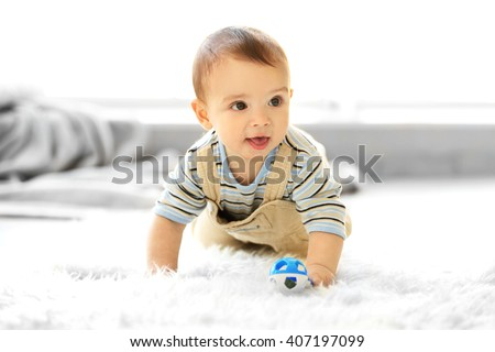 Little baby boy with a toy crawling on the floor at home - stock photo