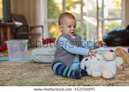Little Baby Boy with a Toy Crawling on the Floor at Home
