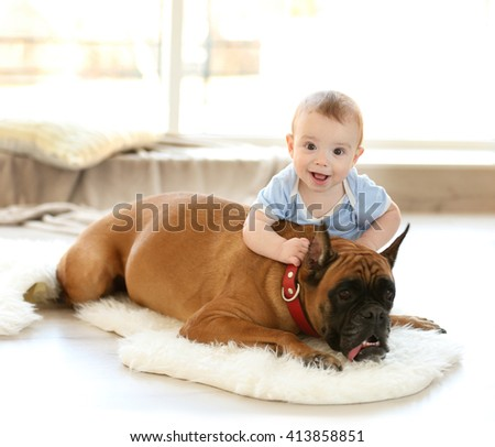 Little baby boy with boxer dog resting on the floor at home - stock photo