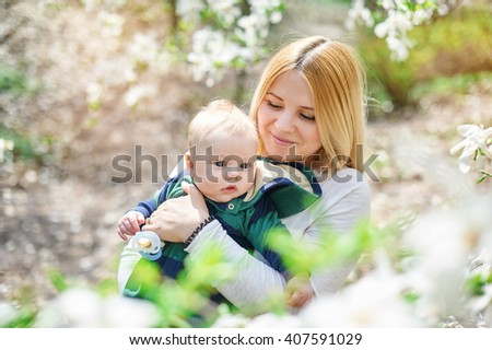 Little baby boy with her young mother in the blossoming Spring garden - stock photo