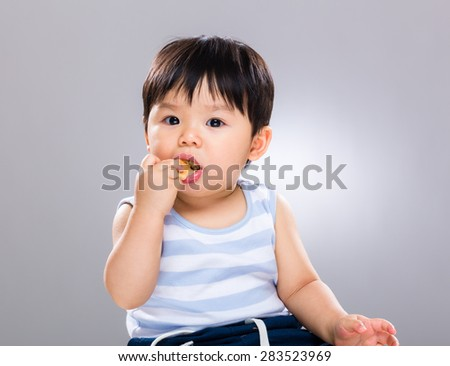 Little baby boy with his cookie - stock photo