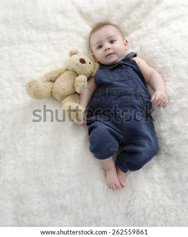 little baby boy with teddy bear lying on his back - stock photo