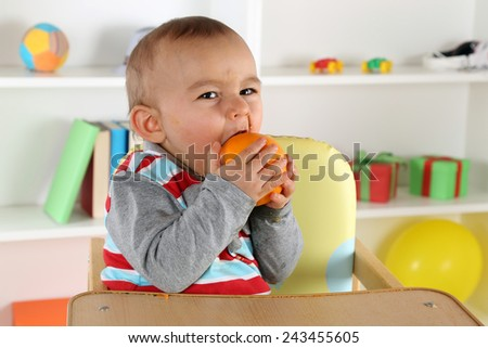 Little baby child eating healthy orange fruit - stock photo