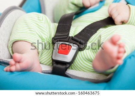 Little baby child fastened with security belt in safety car seat - stock photo