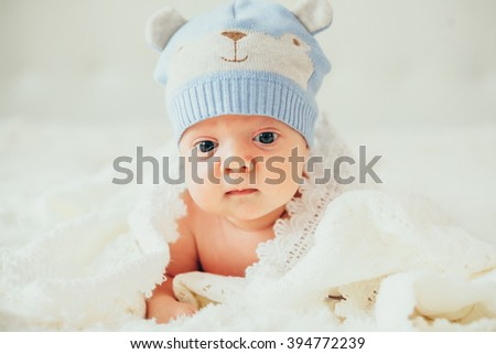 little baby (child) lying in a white knitted blanket. newborn. son. boy. - stock photo