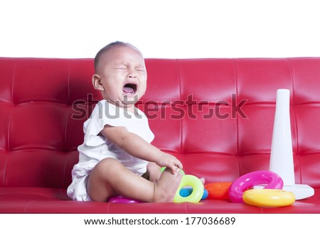 Little baby crying sitting on red sofa with toys - stock photo