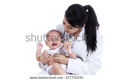 Little baby crying while examined by doctor, isolated over white background - stock photo