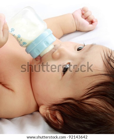Little baby drinking milk from bottle. - stock photo
