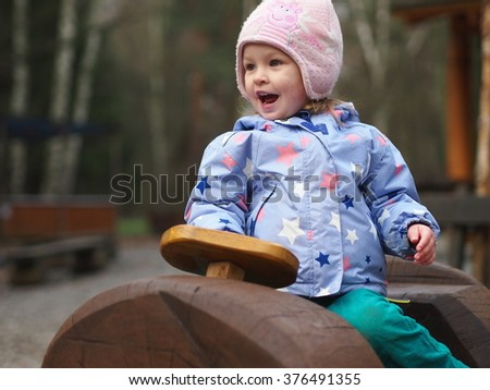 Little baby driver on a wooden vehicle - stock photo