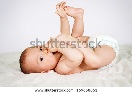 Little baby eating her feet on the bed