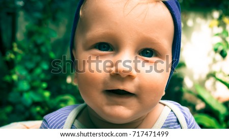 Little baby face close up.Seven-month-old white child with blue eyes in blue hat outside.