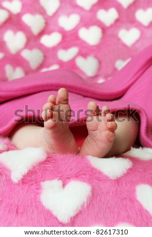 Little baby feet lying on pink fur blanket