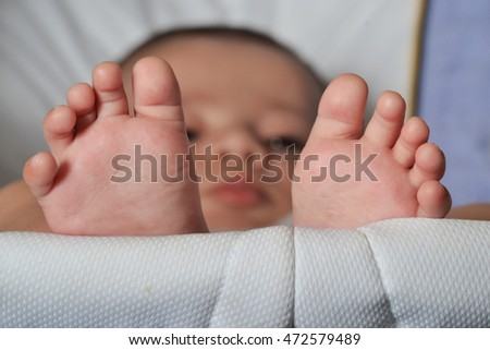 Little baby feet portrait lying down on baby trolley.
