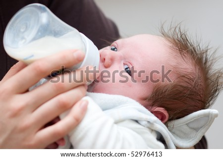 little baby get milk from a bottle with baby bib - stock photo