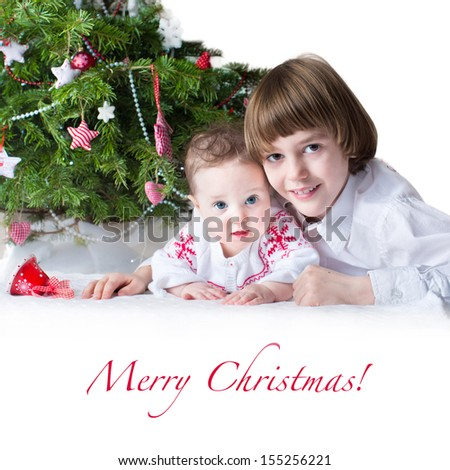 Little baby girl and her cute brother under a decorated Christmas tree with white space for your text - stock photo