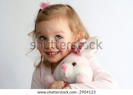 Little baby girl and pink bunny toy - stock photo