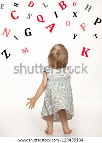 Little baby girl catching letters of alphabet, rear view; white background