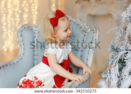 Little baby girl charming blonde in a red dress is looking at silver Christmas trees in the interior of the house - stock photo
