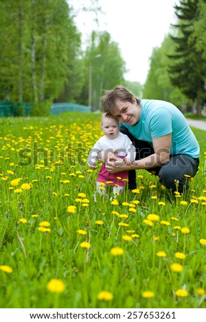 Little baby girl child walking in the green meadow with his father.  - stock photo