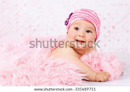 Little baby girl crawling on the floor wearing pink knitted cap - stock photo