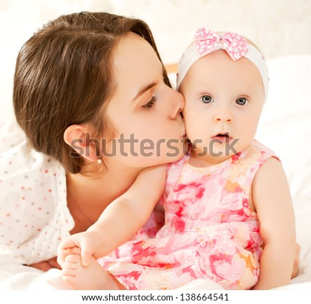 Little baby girl drinking by herself and holding red cap - stock photo