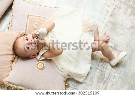 Little baby girl eating a shoe - stock photo