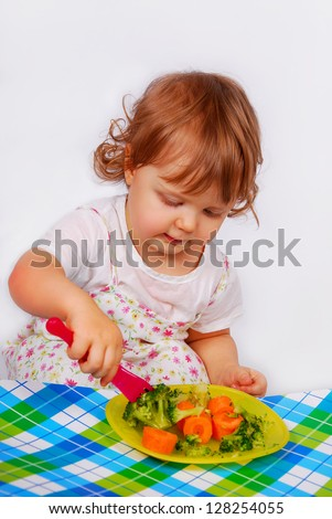 little baby girl eating by itself broccoli and carrot using a fork isolated on white - stock photo