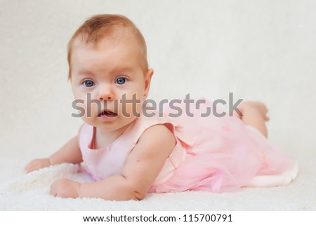 Little baby girl enjoying tummy time in a pink dress - stock photo