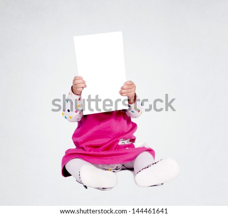 Little baby girl holding blank paper over her head - stock photo
