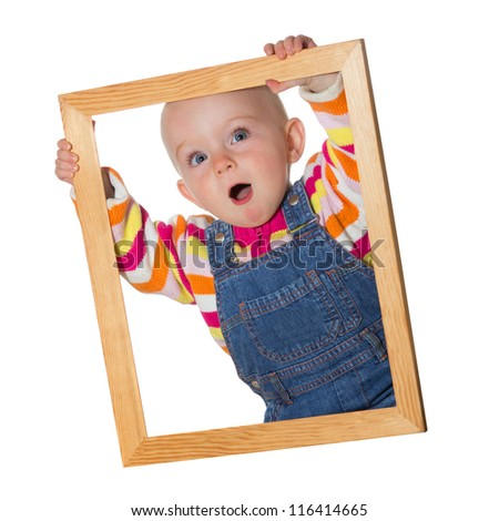 Little baby girl holding up an empty wooden picture frame around her face with a look of amazement isolated on white - stock photo