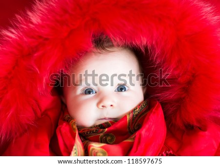 Little baby girl in a red fur jacket - stock photo